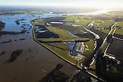 Nederland, Gelderland, De Voorster Klei , 20-01-2011; IJssel bij hoogwater ten noorden van Zutphen. Ingang Twentekanaal aan de horizon, rechts de Voorsterklei. Onder in beeld gemaal Middelbeek. De dijk links van het gemaal zal in het kader van Ruimte voor de Rivier verlaagd worden en er wordt een nieuwe dijk aangelegd (meer landinwaarts, parallel aan het afwateringskanaal). Door de dijkverlegging zal er bij toekomstig hoogwater een waterstanddaling optreden..Pumping-station Middelbeek  (bottom) on the bank of the river IJssel near Zutphen, high waters. In the area left of pumping station the dike will be partially excavated, creating more 'room for the river', decreasing water levels in case of future high waters (flood). A new dike will  be build further away from the river..luchtfoto (toeslag), aerial photo (additional fee required).copyright foto/photo Siebe Swart