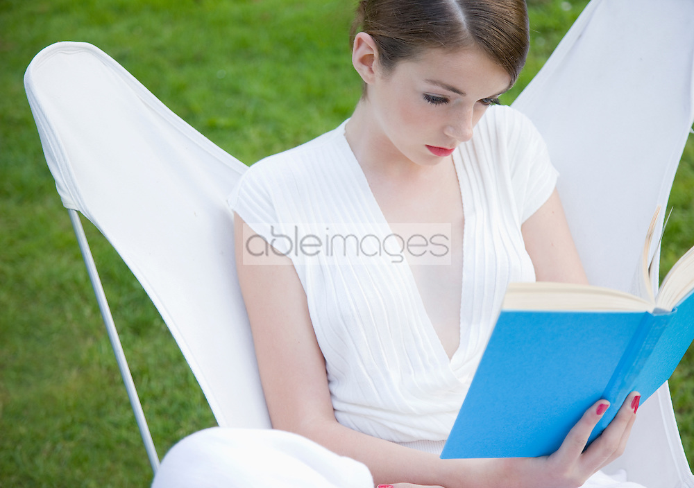 Teenaged girl sitting on high back chair reading a book