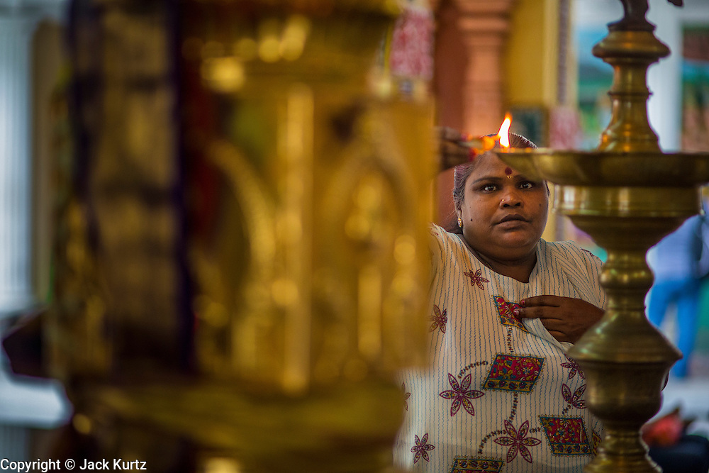 20 DECEMBER 2012 - KUALA LUMPUR, MALAYSIA: A woman prays at the Sri Mahamariamman Temple in Kuala Lumpur. The Sri Mahamariamman Temple is the oldest and richest Hindu temple in Kuala Lumpur, Malaysia. Founded in 1873, it is situated at edge of Chinatown in Jalan Bandar (formerly High Street). In 1968, a new structure was built, featuring the ornate 'Raja Gopuram' tower in the style of South Indian temples. From its inception, the temple provided an important place of worship for early Indian immigrants and is now an important cultural and national heritage in Malaysia.   PHOTO BY JACK KURTZ