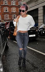 Singer Lily Allen wearing sunglasses with one square lens and round lens, white cropped top, ripped jeans and black platform shoes arriving at BBC Radio 2 in central London, UK. 26/08/2014<br />