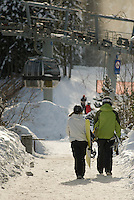 Snowboarders and skiers walk to the Blackcomb Excalibur Gondola at the base of the mountain.
