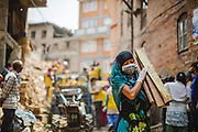 Volunteers and NGO workers help to clear the rubble from buildings destroyed by the 2015 Nepal earthquake.