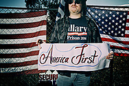 A demonstrator displays a sign in support of America First during a rally at the San Ysidro Port of Entry along the United States-Mexico border in San Ysidro, California on Saturday, December 15, 2018.