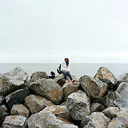 WAINWRIGHT, AK - 2013: Youths hanging out on the Wainwright sea wall.
