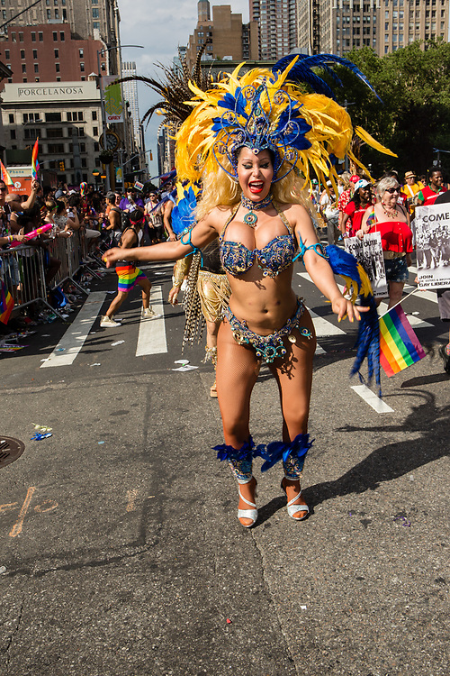 New York, NY - 25 June 2017. New York City Heritage of Pride March filled Fifth Avenue for hours with groups from the LGBT community and it's supporters. A woman dancing in a skimpy costume with a feathered headdress.