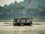 11 MARCH 2016 - LUANG PRABANG, LAOS: People and cars on a ferry across the Mekong River near Luang Prabang. Laos is one of the poorest countries in Southeast Asia. Tourism and hydroelectric dams along the rivers that run through the country are driving the legal economy.       PHOTO BY JACK KURTZ