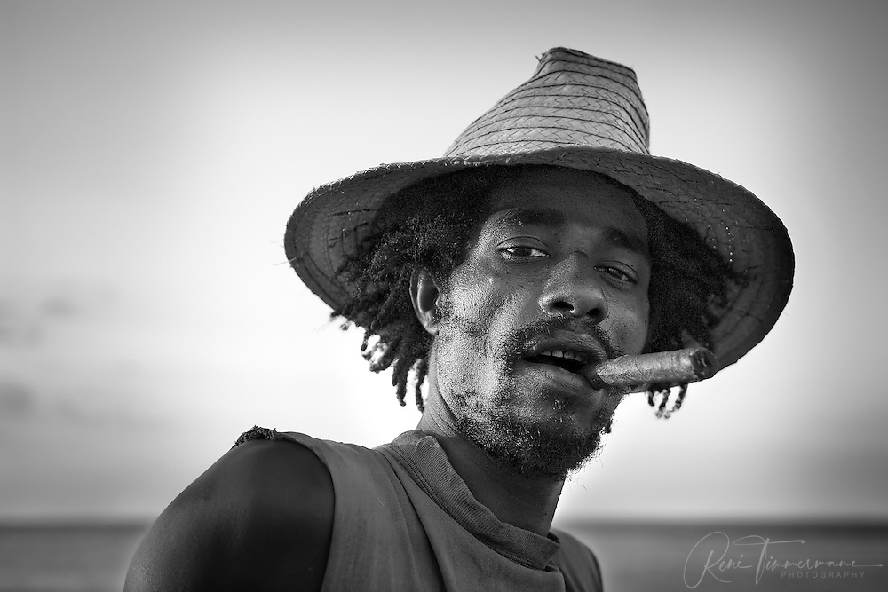A young man is hanging out on the Malecón in Havana while enjoying a Cuban cigar.