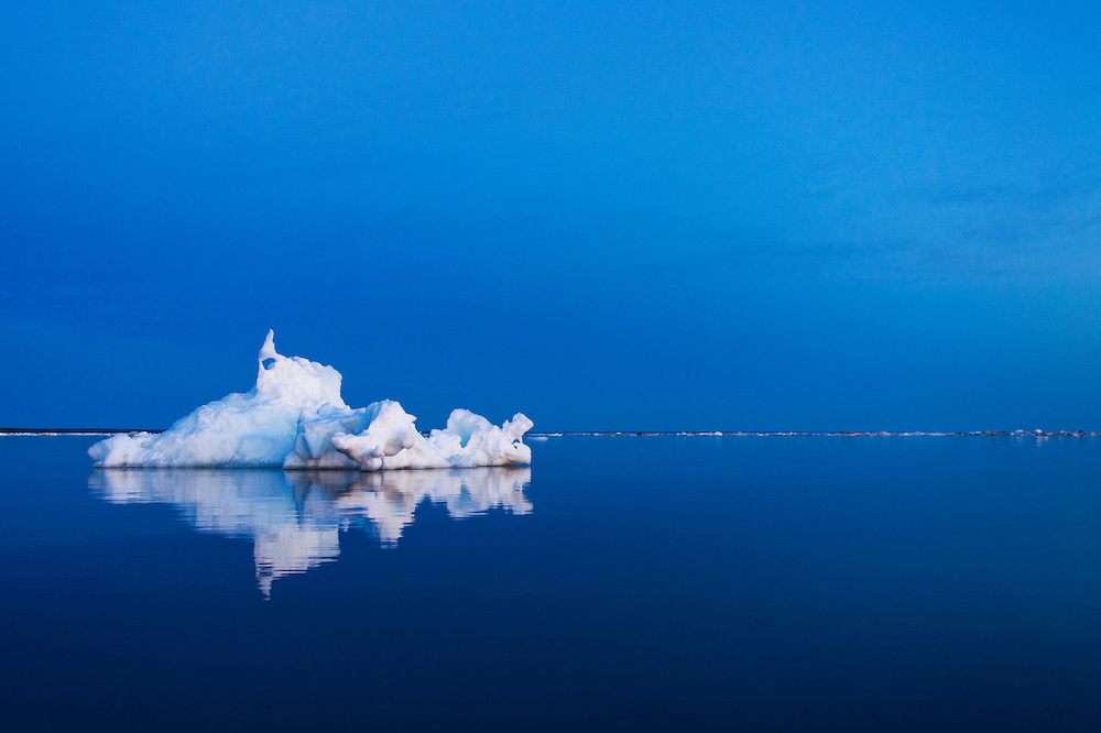 Canada, Manitoba, Churchill, Melting iceberg reflected in still waters of Hudson Bay after sunset on summer evening