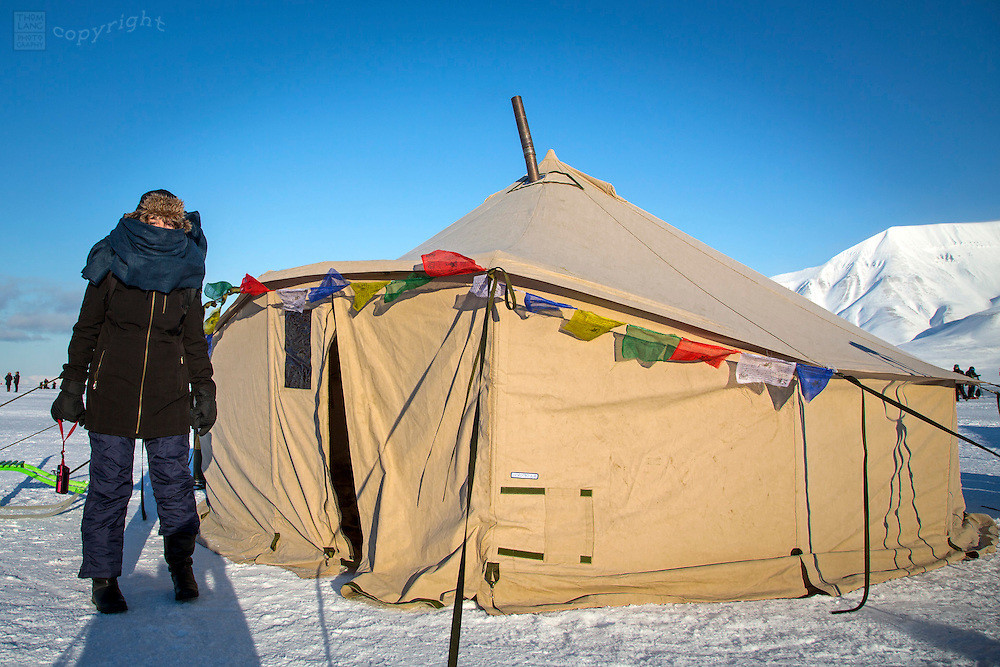 Woman bundled up next to heating tent in Svalbard, Norway during the 2015 total solar eclipse