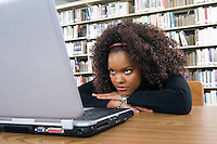 Female university student learning in library