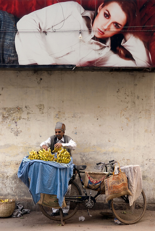 A hawker with bicycle  selling banana's (Kela) in Khan market, a posh market in central Delhi. December 2006