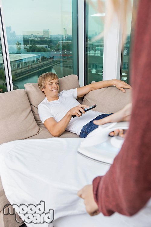Woman ironing shirt while happy man watching TV on sofa at home