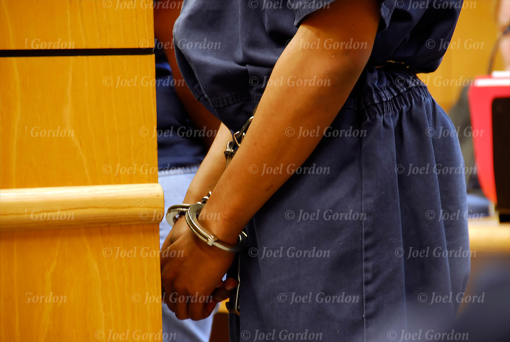 Female juvenile in jail blues handcuffed and leg irons standing before the judge with mother in the Juvenile Justice Center