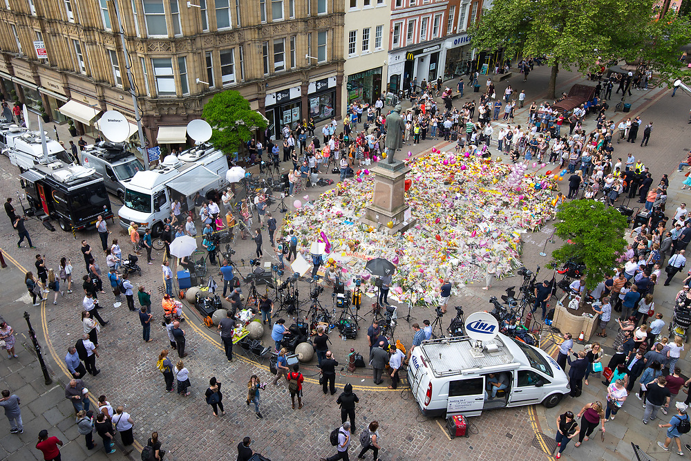 © Licensed to London News Pictures . 25/05/2017 . Manchester , UK . People and media gather round flowers and tributes spread across the width of St Ann's Square in Manchester City Centre , following a terrorist attack at an Ariana Grande concert at Manchester Arena that killed twenty two people . Photo credit : Joel Goodman/LNP