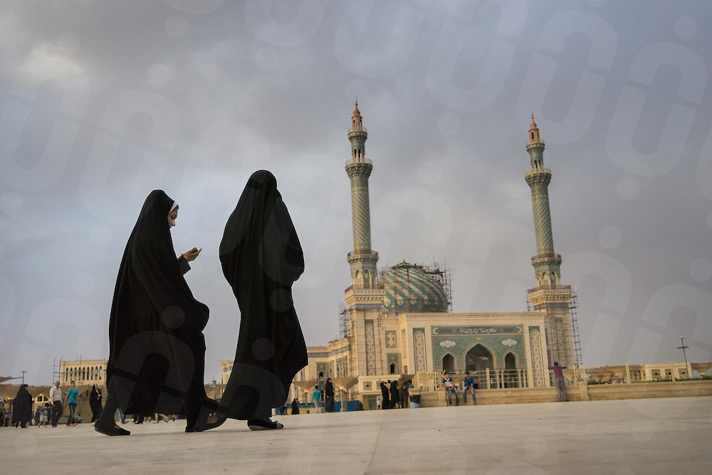 June 11, 2014 - Qom, Iran. Two young pilgrims walk in front of a mosque in Qom, the second holiest city in Iran. The girl on the left is seeing wearing a patch, after having plastic surgery done on her nose. Iran has the world's highest nose surgery rate. © Thomas Cristofoletti / Ruom