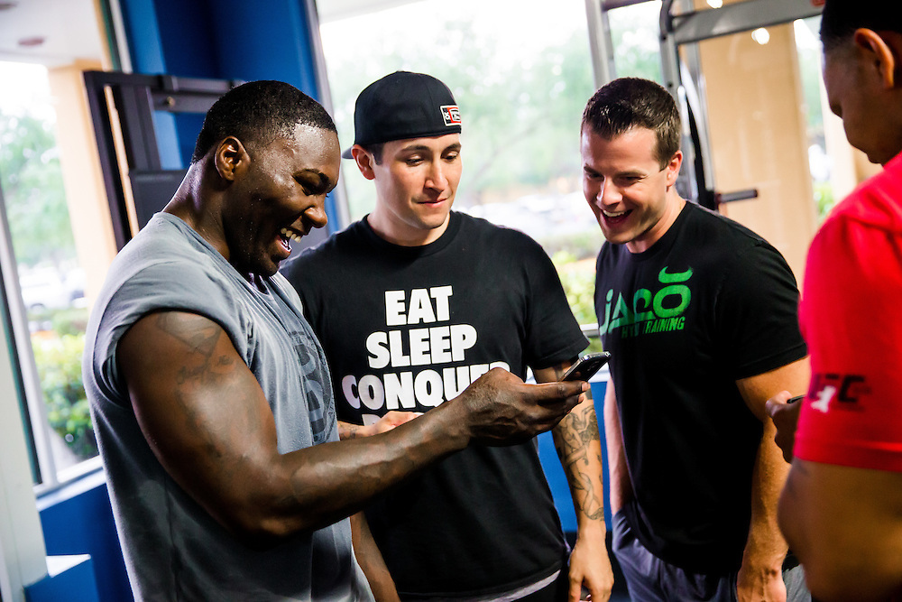 "BOCA RATON, Fla. (April 27, 2015) – MMA fighter Anthony ""Rumble"" Johnson shares a laugh with team photographer Ryan Loco and trainers Jake Bonacci, right, and Dareick Barr, far right, as they look at social media posts regarding his fight during training for his upcoming match against Jon Jones - who was replaced by Daniel Cromier after Jones' legal issues - at Jaco Hybrid Training Center in Boca Raton, Florida. (Photo by Chip Litherland for ESPN the Magazine)"