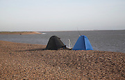 Small tents used for shelter by fishermen on the beach at Shingle Street, Suffolk, England. The tip of Orford Ness spit at the mouth of the River Ore is shown in the background.