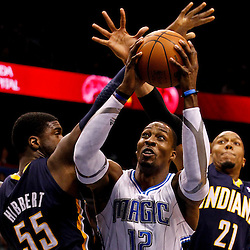 March 11, 2012; Orlando, FL, USA; Orlando Magic center Dwight Howard (12) shoots over Indiana Pacers center Roy Hibbert (55) and power forward David West (21) during the first quarter of a game at  Amway Center.   Mandatory Credit: Derick E. Hingle-US PRESSWIRE