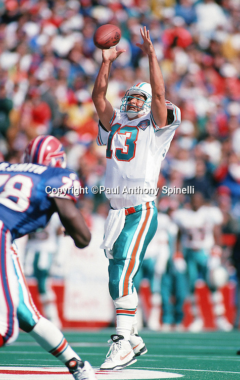 Miami Dolphins quarterback Dan Marino (13) reaches over his head while trying to catch a high snap in the shotgun formation during the NFL football game against the Buffalo Bills on Oct. 9, 1994 in Orchard Park, N.Y. The Bills won the game 21-11. (©Paul Anthony Spinelli)