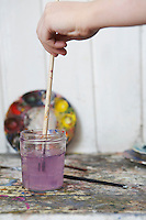 Hand rinsing paintbrush in jar of water