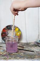 Hand rinsing paintbrush in jar of water