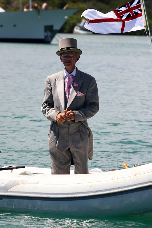 A man in a top hat salutes the passing yachts during the  2008 Antigua Classic Yacht Regatta . This race is one of the worlds most prestigious traditional yacht races. It takes place annually off the cost of Antigua in the British West Indies. Antigua is a yachting haven, historically a british navy base in the times of Nelson.