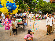 15 MARCH 2015 - SIEM REAP, SIEM REAP, CAMBODIA: Children selling inflated toys at the annual mass merit making at Wat Bo in Siem Reap. More than 1,200 Buddhist monks, from across Siem Reap province, received alms from Buddhist lay people during the morning long ceremony. Wat Bo was originally built to be a the temple for Siamese (Thai) troops when Siem Reap and western Cambodia were controlled by Siam (Thailand). Now Wat Bo is one of the most important temples in Siem Reap.      PHOTO BY JACK KURTZ