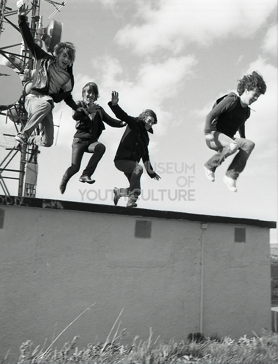 Four young men jumping off low roof onto grass smiling.