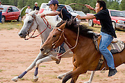 "09 SEPTEMBER 2007 -- ST. MICHAELS, AZ: Jockeys DOMINICK WHITEHORSE, left, and JOHNNY GOLDTOOTH cross the finish line of the five mile race at a traditional Navajo Horse Race in the summit area of the Navajo Indian reservation about 10 miles west of St. Michaels, AZ. Whitehorse won the race. Traditional horse racing is making a comeback on the Navajo reservation. The races are run on improvised courses that vary depending on the local terrain. Use of saddles is optional (except in the ""Cowhand Race"" which requires a western style saddle) and many jockeys ride bareback. The distances vary from one mile to as long as thirty miles. Traditional horse races were common until the 1950's when they fell out of favor, but there has been a resurgence in traditional racing since the late 1990's and now there is a traditional horse racing circuit on the reservation. The race was organized by the Begay family of Steamboat, AZ and run on private land about three miles from a paved road.  Photo by Jack Kurtz"