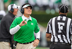 Oct 24, 2015; Huntington, WV, USA; North Texas Mean Green head coach Mike Canales speaks with a referee during the first quarter against the Marshall Thundering Herd at Joan C. Edwards Stadium. Mandatory Credit: Ben Queen-USA TODAY Sports