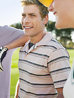 Group of young golfers on court focus on smiling man