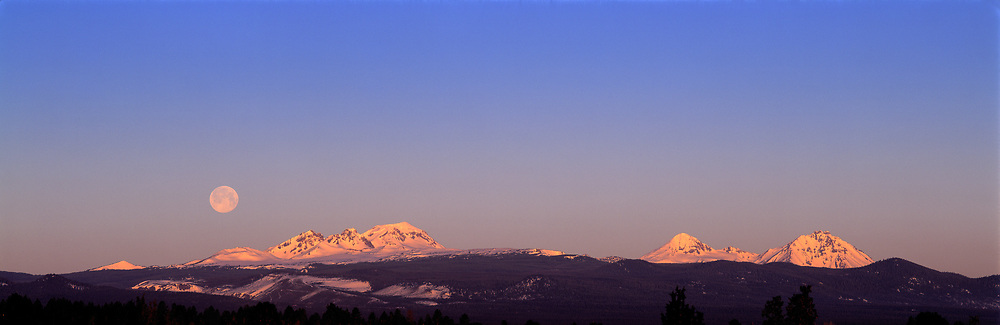 The moon sets behind Broken Top and the Three Sisters near Bend, Oregon. ©Ric Ergenbright