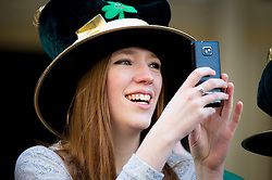© Licensed to London News Pictures. 16/03/2014. London, UK. A spectator captures the annual St Patrick's Day parade as it moves through London from Green Park to Trafalgar Square. Photo credit : David Tett/LNP