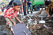 Apr. 30 - BANGKOK, THAILAND: A Red Shirt child cleans up some of the diesel fuel soaked dirt left by a Red Shirt barricade in the Sala Daeng intersection in Bangkok. The Red Shirts moved one of their barricades in the Sala Daeng Intersection in Bangkok Friday In one of the first positive moves to take place since the Red Shirts occupied central Bangkok in early April. The barricade was moved far enough back to open one lane of traffic on  Ratchadamri Street to allow ambulance access to King Chulalongkorn Memorial Hospital, a large hospital at the intersection. Many of the patients in the hospital have been moved to other hospitals because a group of Red Shirts entered the hospital Thursday looking for Thai security personnel, who were not in the hospital. The stand off between the Red Shirts and the government enters its third month in May. The Red Shirts continue to call for Thai Prime Minister Abhisit Vejjajiva to step down and dissolve parliament and demand the return of ousted Prime Minister Thaksin Shinawatra.   PHOTO BY JACK KURTZ