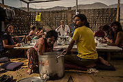 Colombian and Chilean volunteers Angelica and Daniel serve meals to their meditation student colleagues as they are gathered to build a meditation centre in the desert of Cieneguilla, a quiet location in the outskirts of Lima, Peru, Wednesday, November 4, 2015.
