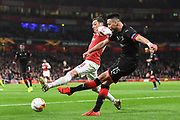 Rennes Ramy Bensabaini (15) and Arsenal Midfielder Mesut Ozil (10) in action during the Europa League round of 16, leg 2 of 2 match between Arsenal and Rennes at the Emirates Stadium, London, England on 14 March 2019.