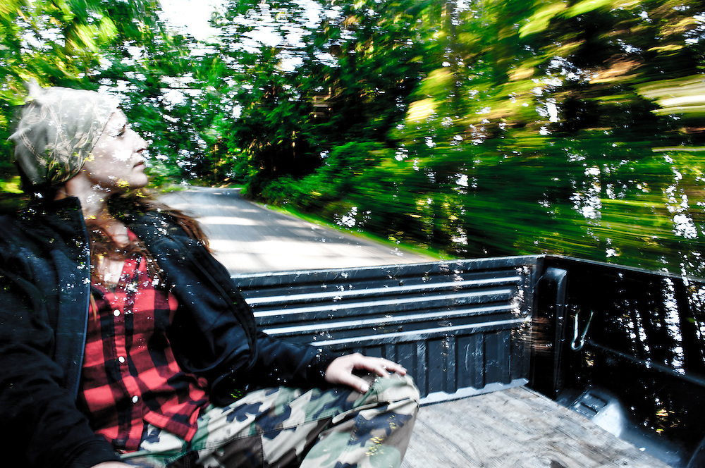 A multiple exposure of a woman sitting in the back of a truck and trees.
