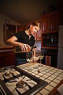 USA, Oregon, Eugene, young woman pouring white wine. MR