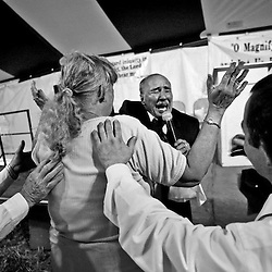 """The Rev. Joe Adkins (middle, facing camera) lays hands on """"Sister Smith"""", as she is held from falling by Bobby Lee Biar Jr. (right), and The Rev. Dave Harold (left) during a """"Holy Ghost Hoedown"""" tent revival in Lynchburg, Virginia. """"Let the Power of Heaven and God fill her. Fill her. Fill her!"""" Rev. Adkins shouts. After """"Sister Smith"""" whispers her ailments into Rev. Adkins' ear, he lays hands on her. """"Expect the miracle. Believe in the miracle!"""" he insists. """"In Jesus' name you're healed!"""" he cries. She walks away, swaying, fingers fluttering, speaking in tongues."""