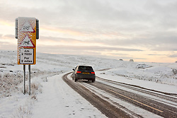 © Licensed to London News Pictures. 27/02/2020.  Builth Wells, Powys, Wales, UK. A motorist drives  through a wintry landscape on the Mynydd Epynt moorland along the B4520 (Brecon road) between Builth Wells and Brecon after snow fell on high land last night in Powys, Wales, UK. Photo credit: Graham M. Lawrence/LNP