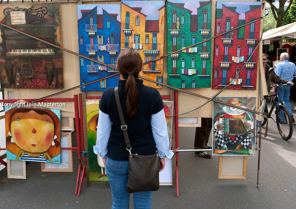 Woman looking at original art at outdoor market at Strasse des 17 Juni in Tiergarten in Berlin