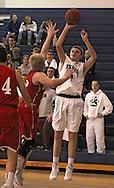Cedar Rapids Xavier's Adam McDermott (3) puts up a shot over the arms of Ottumwa's Sam Moreland (12) during their game at Xavier High School in Cedar Rapids on December 10, 2013.