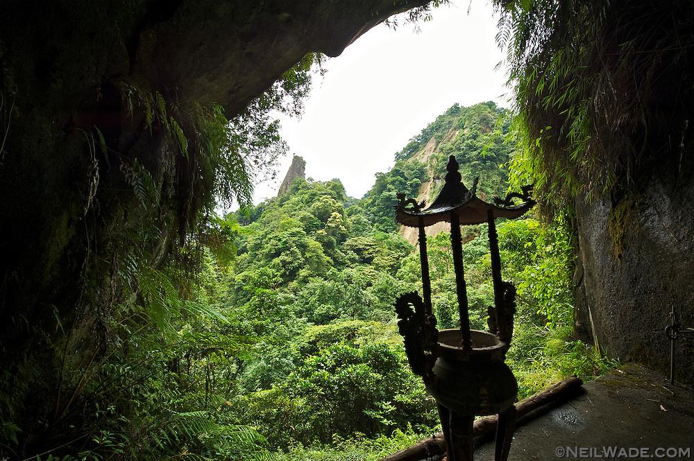 A Daoist incense burner hides in a cave on Xiaozi Shan mountain, near Pingxi, Taiwan.