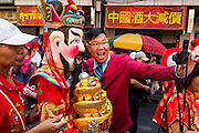 31 JANUARY 2014 - BANGKOK, THAILAND:   A man takes a self portrait with a Chinese deity on Yaowarat Road during Lunar New Year festivities, also know as Tet and Chinese New Year, in Bangkok. This year is the Year of the Horse. Ethnic Chinese make up about 14% of Thailand and Chinese holidays are widely celebrated in Thailand.     PHOTO BY JACK KURTZ