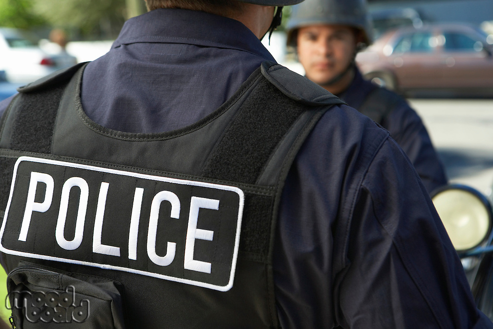 Police officer in bulletproof vest outdoors back view