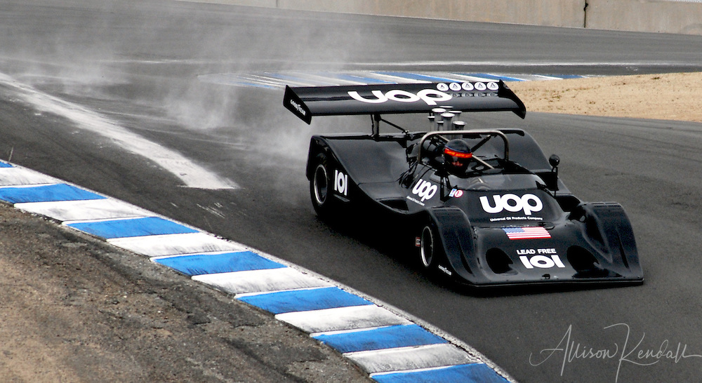A powerful racecar kicks up dust as it descends through the notorious Corkscrew section of Laguna Seca, in Monterey