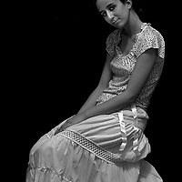 A young woman wearing a long white dress sitting loking at the camera