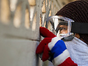 26 DECEMBER 2013 - BANGKOK, THAILAND: A rock throwing anti-government protestor looks through a block wall while taking cover from police who were firing rubbet bullets. Thousands of anti-government protestors flooded into the area around the Thai Japan Stadium to try to prevent the drawing of ballot list numbers by the Election Commission, which determines the order in which candidates appear on the ballot of the Feb. 2 election. They were unable to break into the stadium and ballot list draw went as scheduled. The protestors then started throwing rocks and small explosives at police who responded with tear gas and rubber bullets. At least 20 people were hospitalized in the melee and one policeman was reportedly shot by anti-government protestors.      PHOTO BY JACK KURTZ