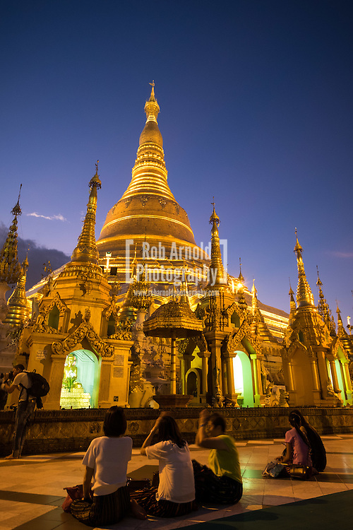 People meditating at the Shwedagon Paya in Yangon during sunset