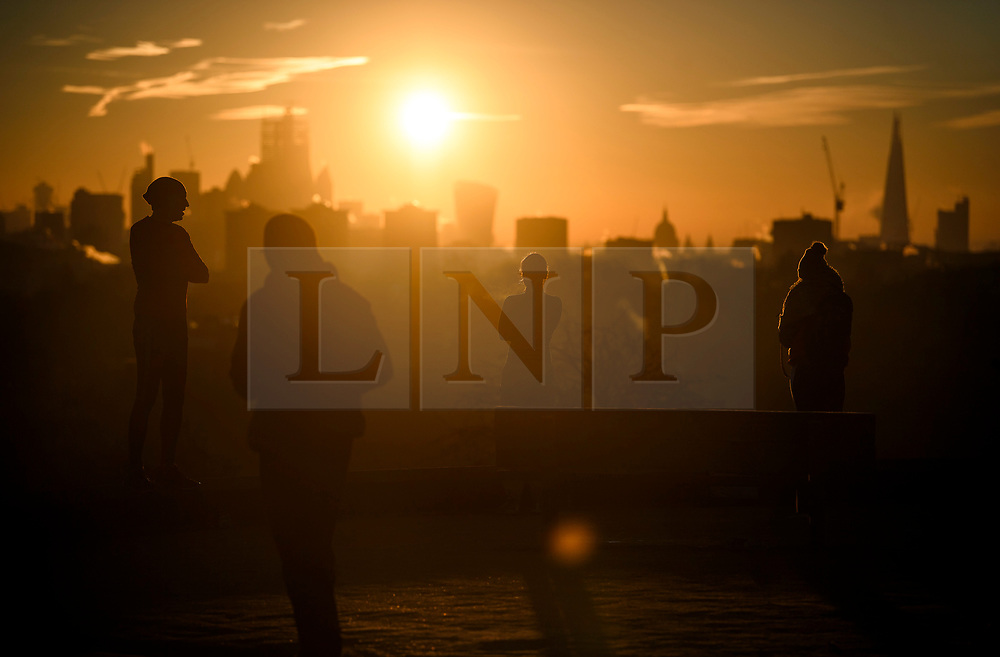 © Licensed to London News Pictures. 03/02/2019. London, UK. Members of the public watch the sun rises from behind the City of London, from Primrose Hill in North London on a cold winter morning. Large parts of the UK continue to be deluged with snow and freezing temperatures. Photo credit: Ben Cawthra/LNP